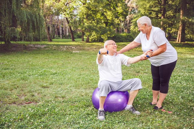 Concept of healthy lifestyle - pensioner man and woman doing tog stock images