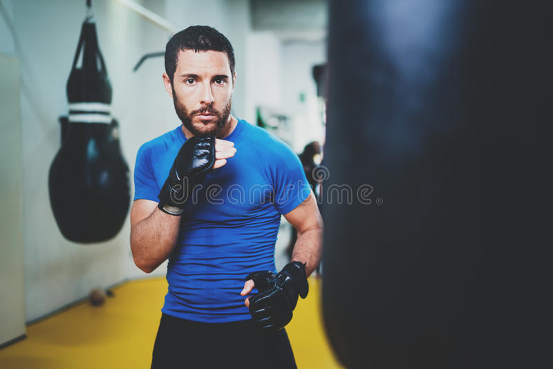Concept of a healthy lifestyle.Young athlete fighter practicing kicks with punching bag.Kick boxer boxing as exercise. For the fight.Boxer man hits punching bag royalty free stock photo