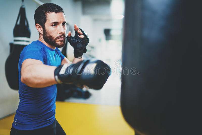Concept of a healthy lifestyle.Young muscular man fighter practicing kicks with punching bag.Kick boxer boxing as. Exercise for the fight.Boxer hits punching stock photography