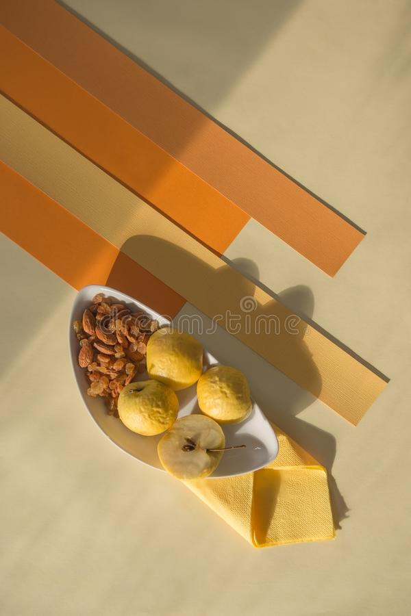 Concept of healthy snack of yellow apples, raisins and almonds stock images