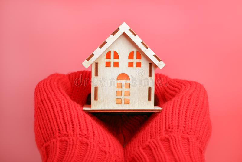Concept heat saving. Warming house. Model house in the hands stock images