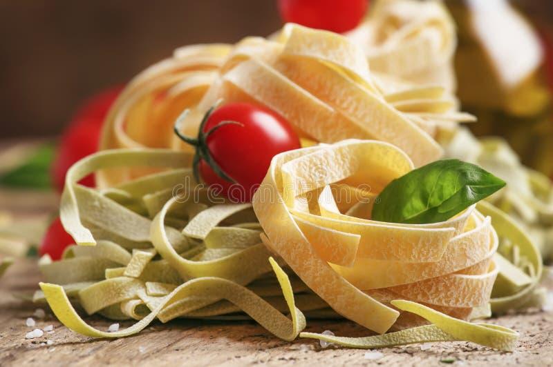 Concept het Italiaanse voedsel koken met groene en gele tagliatelledeegwaren, rode kersentomaat en groen basilicum, rustieke hout stock foto's