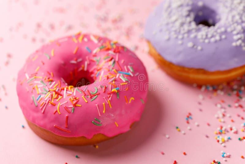 Concept het koken, het bakken en voedsel - close-up Twee donuts in roze en violette glans op een roze achtergrond tendenskleuren stock foto