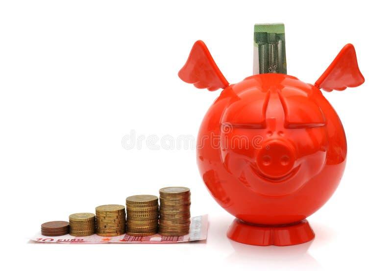 Concept het kweken van winst met muntstukken en piggy stock foto's