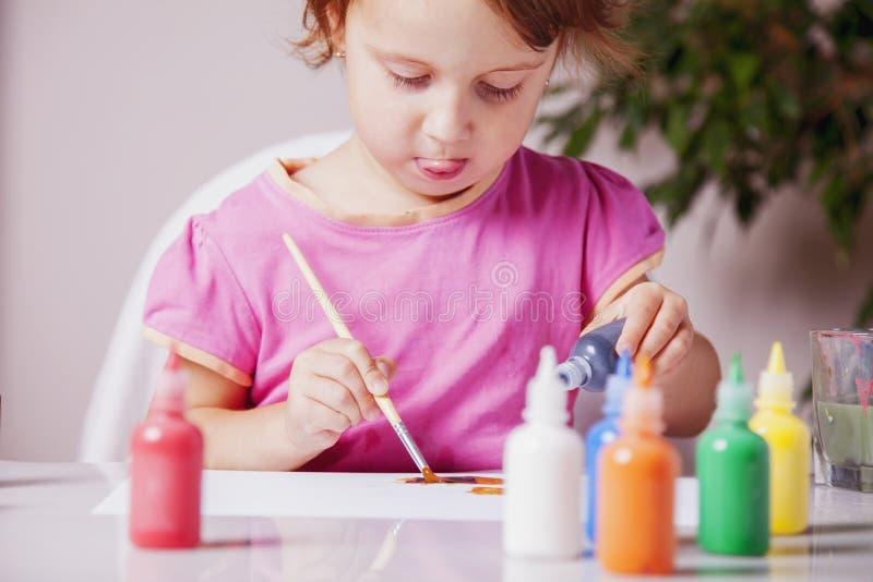 Concept: Het leren is pret! Proceskunst: het gelukkige leuke meisje schilderen royalty-vrije stock afbeelding