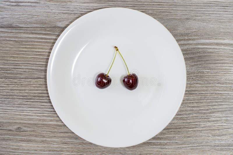Concept het op dieet zijn en het gezonde eten Rode sappige kersen op witte ronde plaat Houten achtergrond, hoogste mening het ver royalty-vrije stock foto's