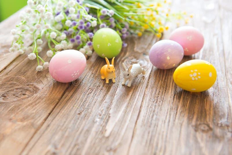 Concept heureux de Pâques Oeufs de pâques avec des fleurs et de petits jouets de lapin sur le panneau en bois, concept de vacance image stock
