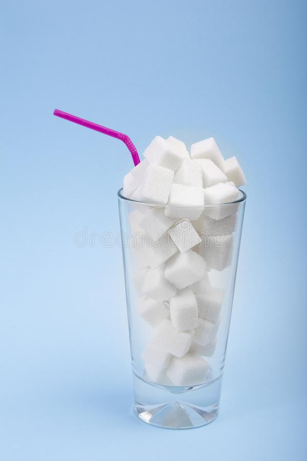 Concept of hidden sugar in soda, a source of energy and fast carbs. Vertical arragement. Sugar cubes. Concept of hidden sugar in soda, a source of energy and royalty free stock photography