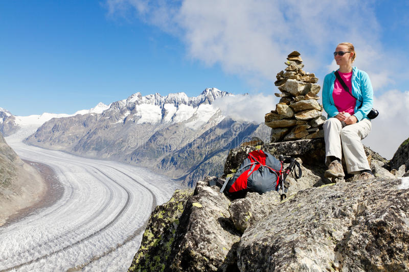 Concept for hiking, climbing,. Walkig and outdoor adventures: woman on mountain top with backpack and sticks above Aletsch glacier Switzerland stock photography