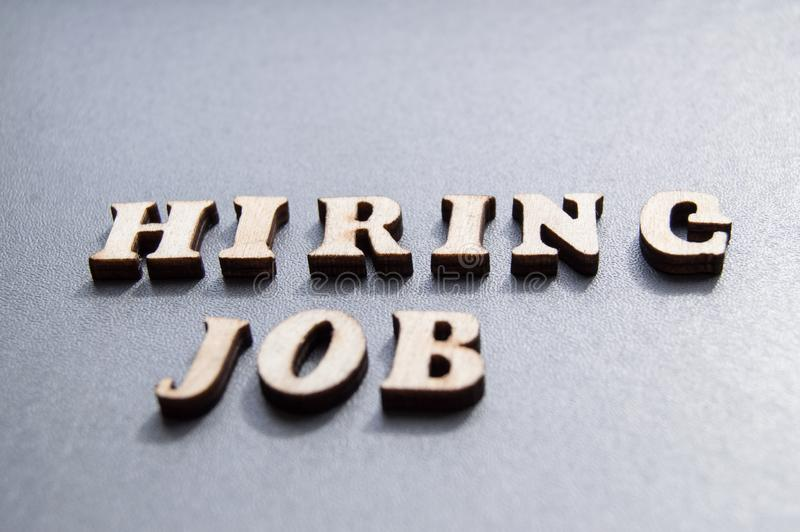 The concept of hiring workers, written by HIRING JOB in wooden letters on a gray background with selective focus and space for royalty free stock images
