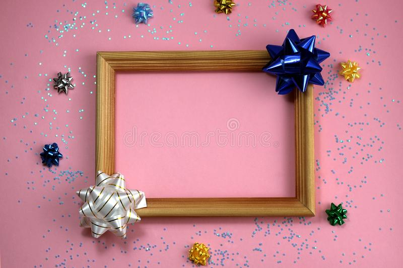 The concept of the holiday, around the wooden frame are holiday bows in the form of a star. Bow, background picture, banner, birthday, celebration, chic stock photo