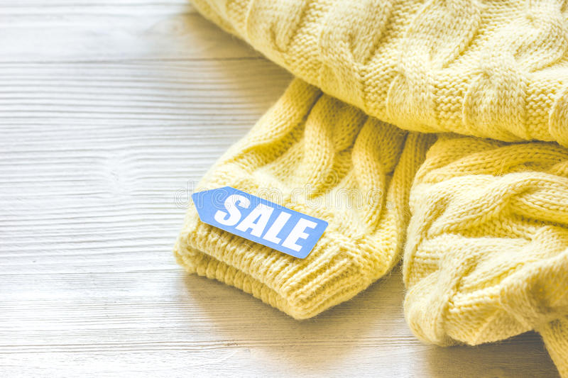 Concept holiday sales of clothes and textiles. On wooden background royalty free stock photography