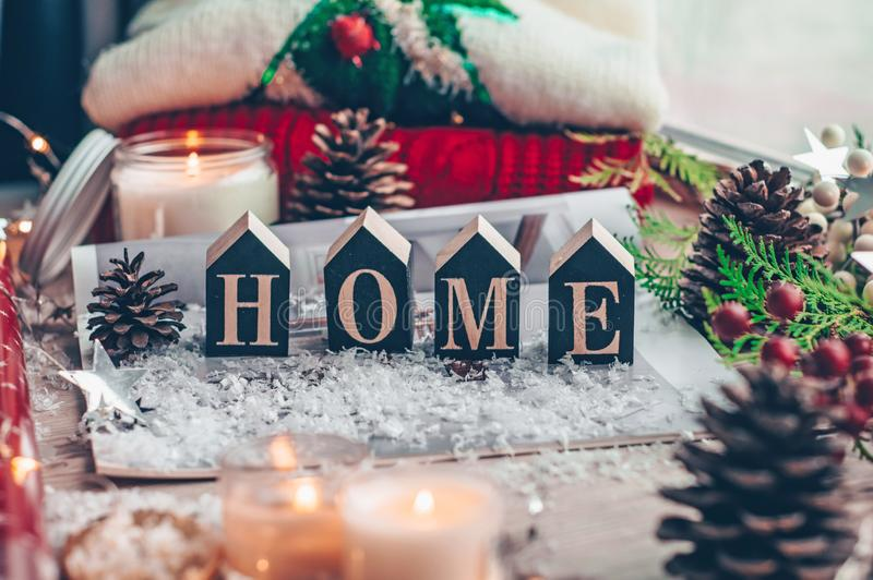 Concept of Home and comfort. Christmas decor Warm sweater, candles, Christmas tree. Word Home. Winter mood, Cozy Home stock image