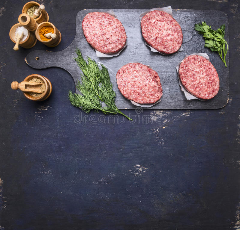 Concept of home cooking chops of marble beef four cutlets are laid out on vintage cutting board on blue rustic wooden background. Concept of home cooking chops royalty free stock image