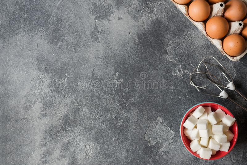 Concept of home cooking, eggs and sugar with a whisk on a dark table. Selective focus.  royalty free stock images
