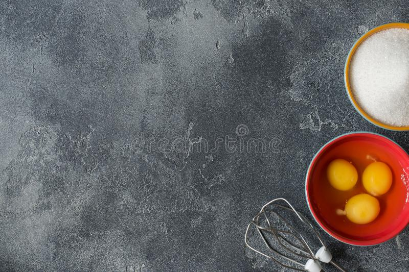 Concept of home cooking, eggs and sugar with a whisk on a dark table Selective focus. Concept of home cooking, eggs and sugar with a whisk on a dark table royalty free stock photo