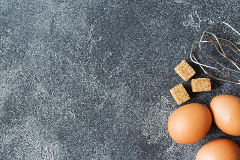 Concept of home cooking, eggs and sugar with a whisk on a dark table. Selective focus.  royalty free stock photo
