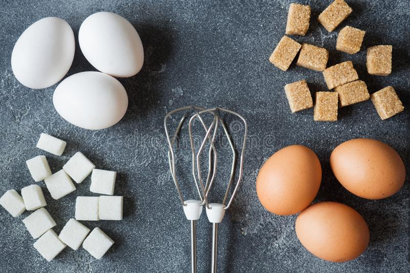 Concept of home cooking, eggs and sugar with a whisk on a dark table Selective focus. Concept of home cooking, eggs and sugar with a whisk on a dark table stock photo