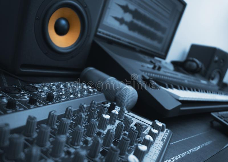 Concept of home music studio. Blue styled. Mixer, condenser microphone and professional monitor. Concept of home music studio. Blue styled stock images