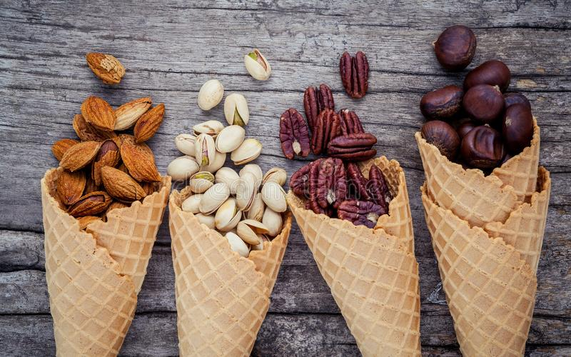Concept for homemade various nuts ice cream. Mixed nuts in waffle cones on shabby wooden background.top view royalty free stock photography