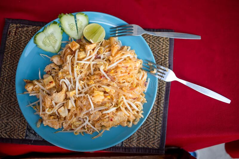 Concept honeymoon in asia, love, february 14, romatic journey. Delicious traditional Thai Pad Thai noodles on a plate. Cucumbers in firm heart and 2 forks. top royalty free stock photography