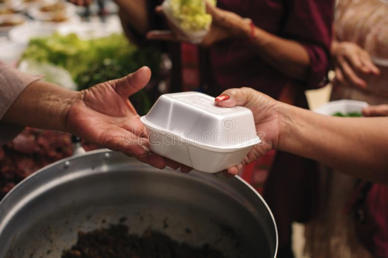 Concept hongersnood en sociale ongelijkheid: het voeden van voedsel voor het concept van de bedelaarsarmoede: De maatschappij van stock foto