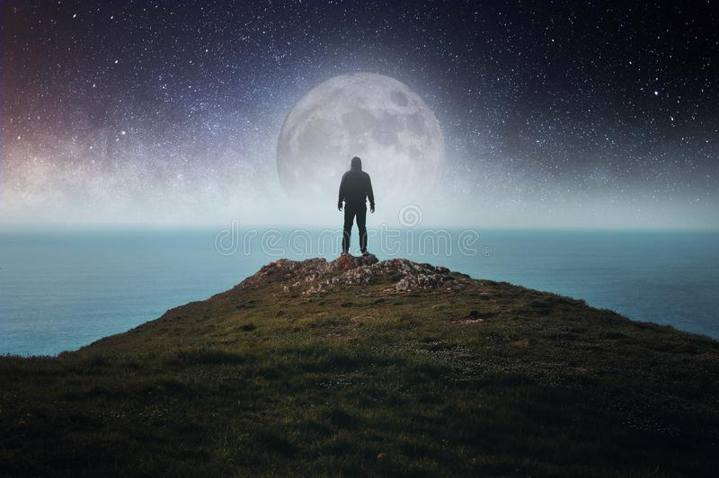 A concept of a hooded figure standing on a hill looking out to sea, with the moon, stars and the universe above stock photography