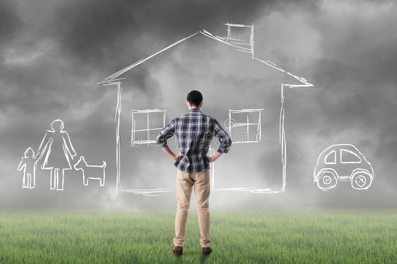 Concept of house. Asian man look toward the drawing house and family in the heaven royalty free stock images