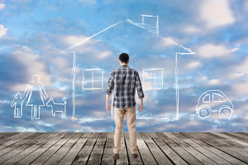 Concept of house. Asian man look toward the drawing house and family in the heaven stock photography