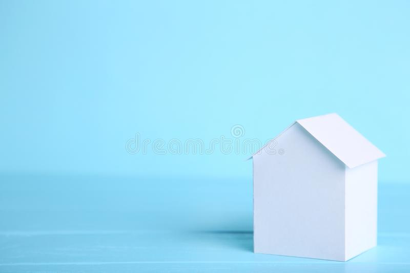 Blue paper house with coins on grey background stock image