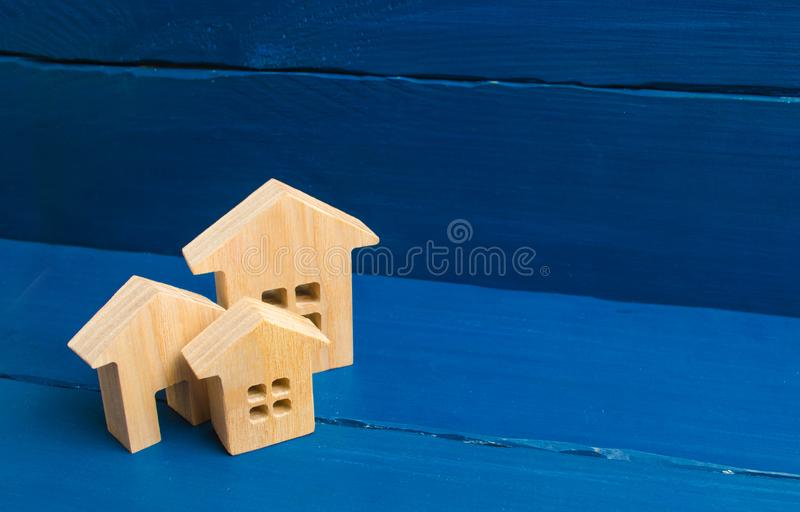 The concept of housing and real estate. Buying and buying a home, selling and investing. Urban growth, urbanization. Wooden houses on a blue background. The royalty free stock photography
