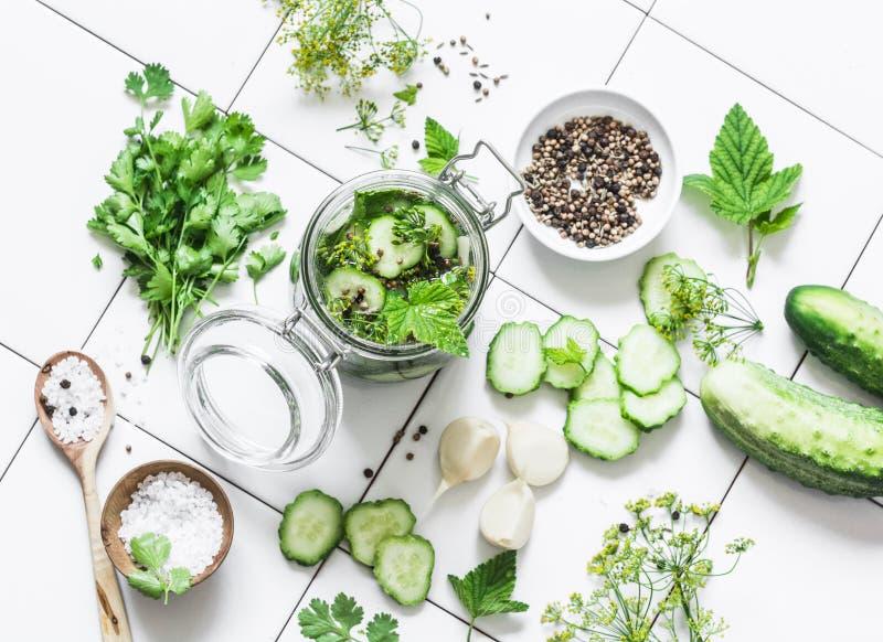 Concept huis het inblikken Kruik van ingelegde komkommers en ingrediënten op een lichte achtergrond, hoogste mening stock foto's