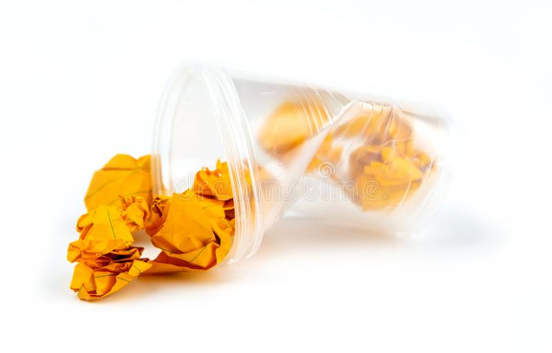 Concept huisvuil en verontreiniging De verfrommelde plastic kop met oranje bladen van document isoleert op witte achtergrond stock foto's
