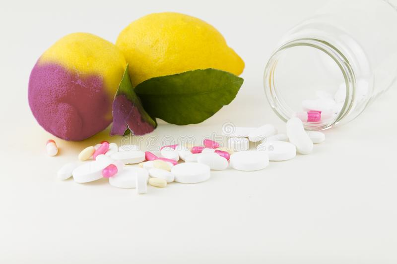Concept: human GMO manipulation of nature and relative poisoned fruits. Close-up of a lemon contaminated by changing color from. The medicines in front of it on royalty free stock image