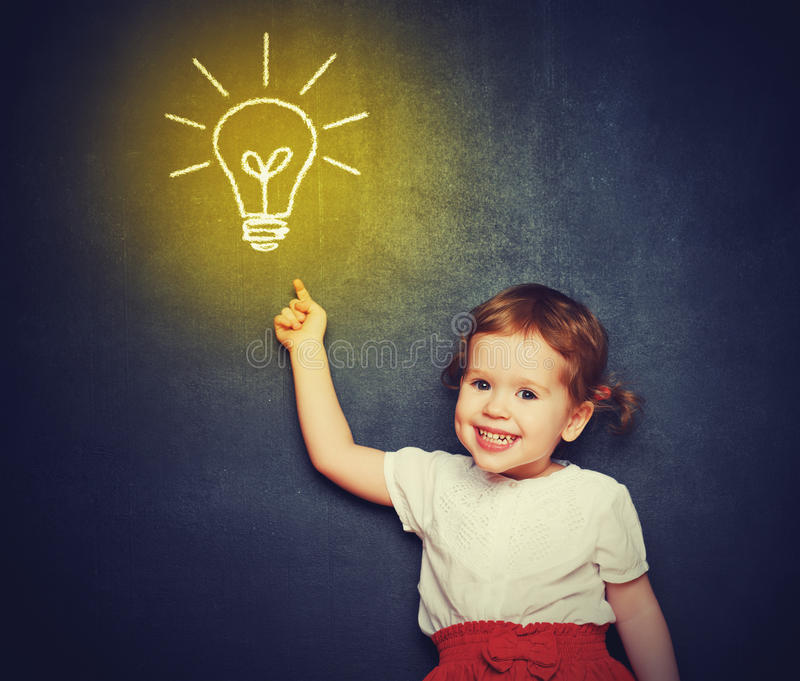Concept, the idea of a happy little girl with a bulb at the blackboard stock photo