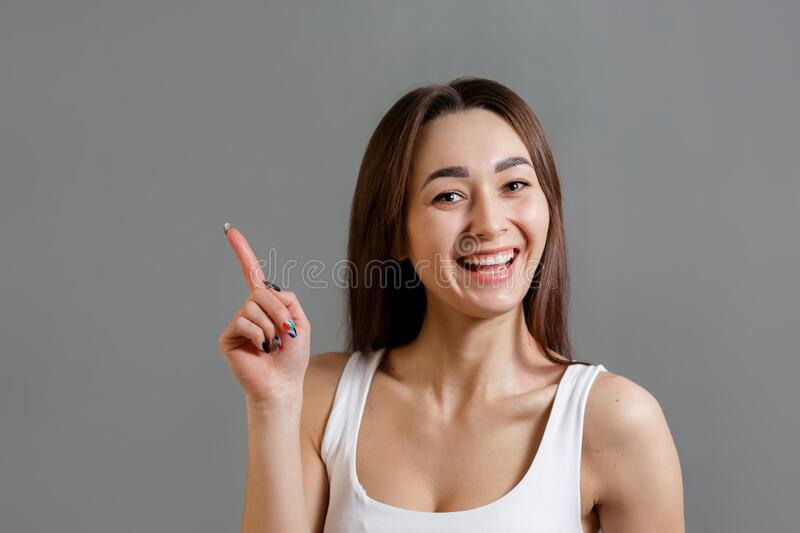 Concept of idea and information search. Portrait of a happy young Caucasian woman pointing up. Gray background. Copy space.  royalty free stock photo