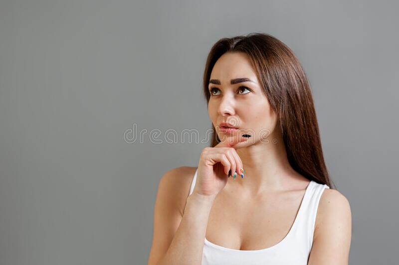 Concept of idea and information search. Portrait of a thoughtful young Caucasian woman. Gray background. Copy space stock photo