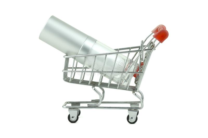 Concept idea shopping, empty a bottle of face cream in miniature shopping cart, isolated with clipping path on white background. stock photos