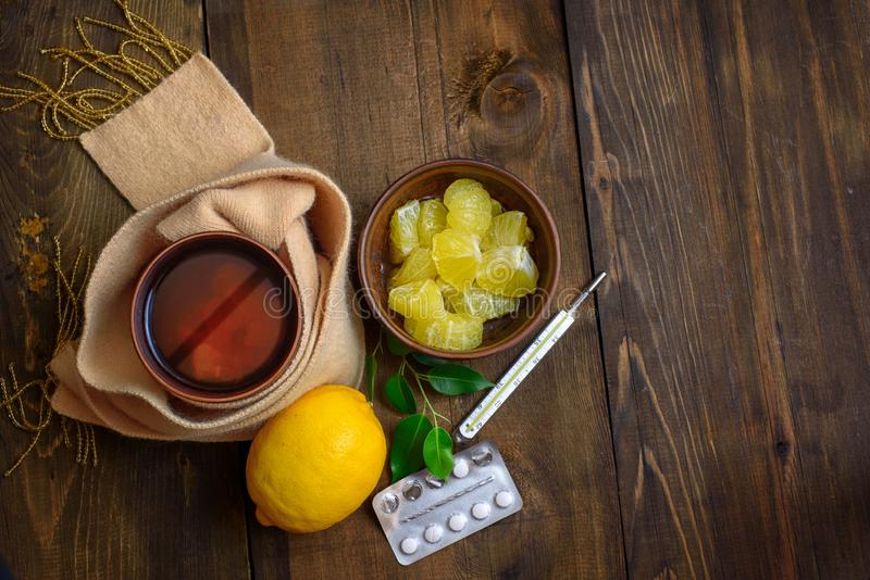 Concept illness, colds, cure, fall and winter. Tea with lemon, thermometer, pills and a knitted scarf. Top View. Concept illness, colds, cure, fall and winter stock image