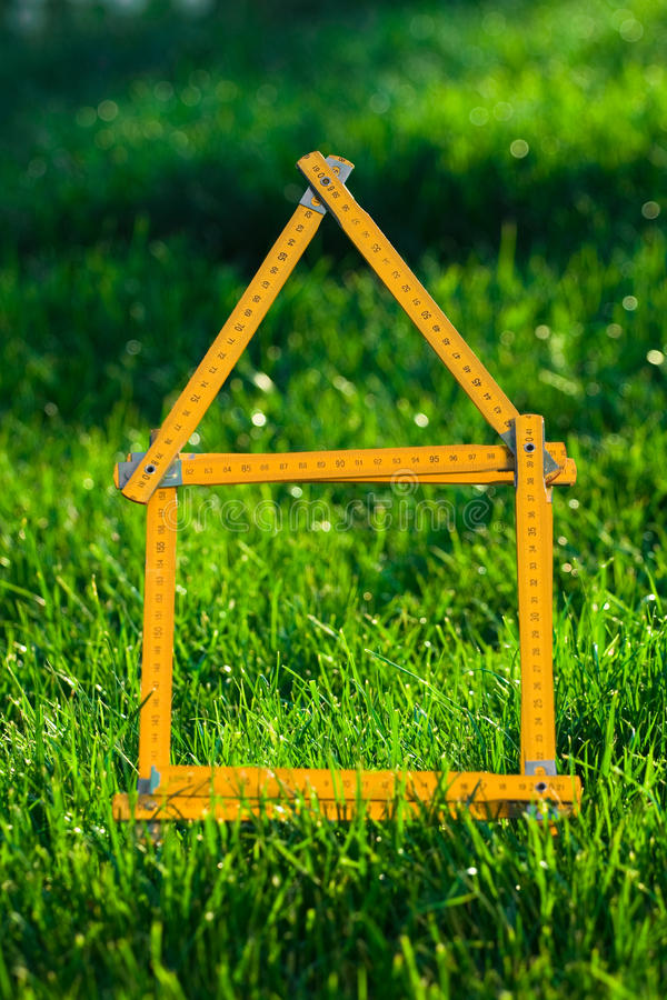 Concept image for building a house. A concept image for building a house on a greenfield stock photography