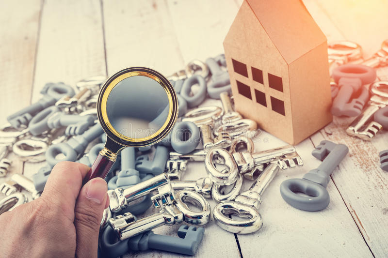 Concept image of a home inspection. A male hand holds a magnifying glass over a miniature house royalty free stock photography