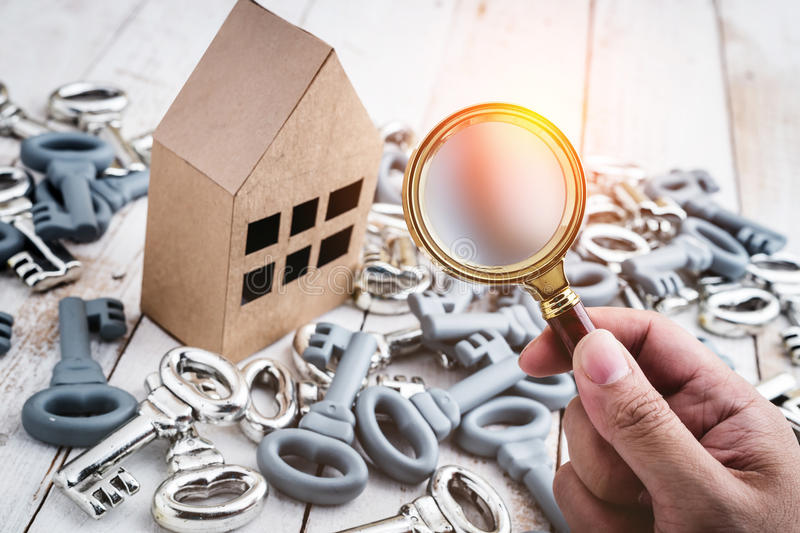 Concept image of a home inspection. A male hand holds a magnifying glass over a miniature house royalty free stock image