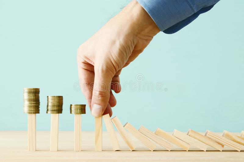 Concept image of investing and banking. A businessman stops the domino effect from risking financial investment. royalty free stock image
