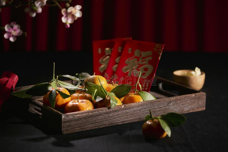 Concept image of the lunar new year -mandarin orange and red packet. Text on envelop means Happy New Year and Happiness royalty free stock image