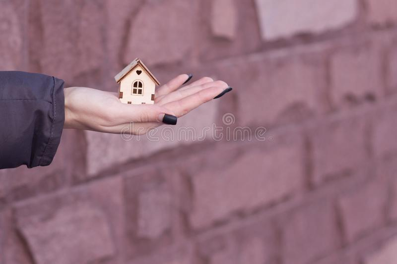 Concept image of my house. A small model of a wooden house stands on a hand.  stock photos