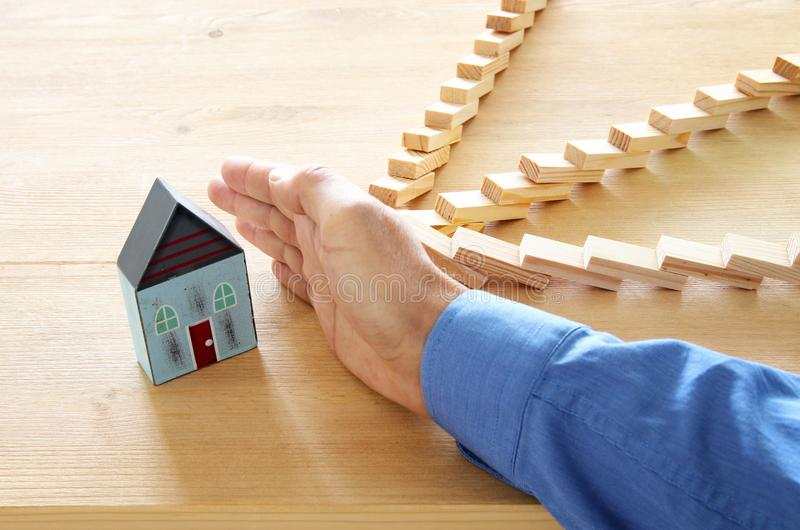 Concept image of real estate insurance and protection. man hands blocking the domino effect, saving a small house. stock images