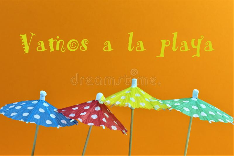 An concept Image of some umbrellas with the text, vamos a la playa = lets go to the beach Translation. Abstract royalty free stock image