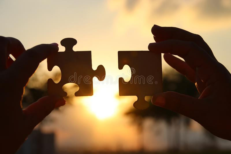 Concept image of a woman hands holding two pieces of a puzzle in front of the sun. Sunset time with lens flare. creativity and con stock images
