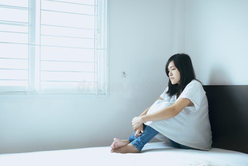 Concept inattendu de grossesse, femme asiatique s'asseyant sur la chambre à coucher à la maison, famille malheureuse et confuse d photos stock
