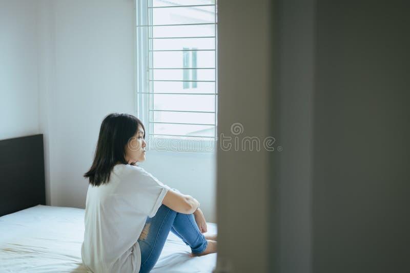 Concept inattendu de grossesse, femme asiatique s'asseyant sur la chambre à coucher à la maison, problème malheureux et confus de photo stock